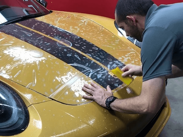 man preserving the paint on a yellow car