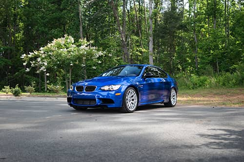 blue bmw parked in front of a forest of trees